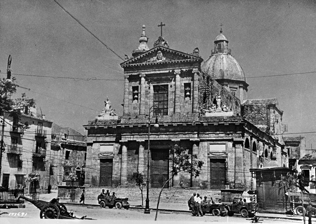 The cathedral in the central area of Gela was one of the first buildings captured by U.S. Army Rangers during operations on the island of Sicily. American troops can be seen moving around outside the cathedral near an abandoned Italian antitank weapon.