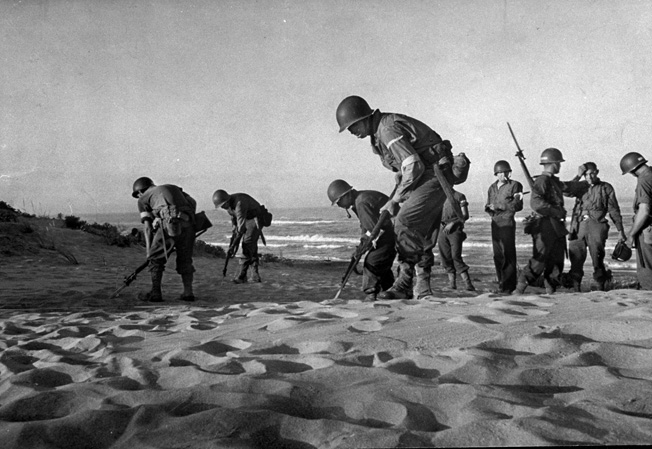 American combat engineers using their bayonets to locate and remove mines ahead of troops coming ashore during the invasion of Sicily. (Photo by Bob Landry//Time Life Pictures/Getty Images)