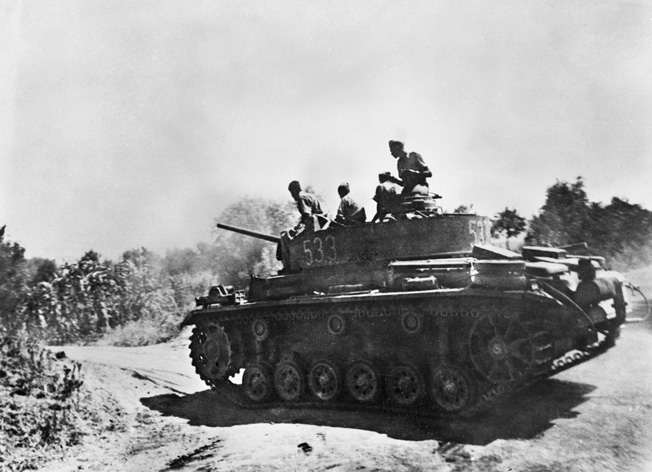 Axis tanks nearly broke through the thin American lines at Gela; however, individual acts of heroism and superior naval gunfire took a heavy toll on German and Italian armor. This German PzKpfw. III raises a cloud of dust as it moves toward the fighting.