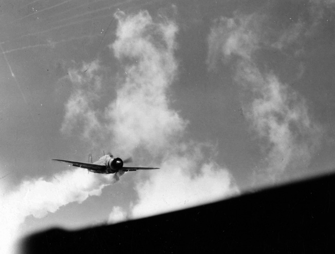 A Japanese dive-bomber, its pilot bent on a suicide crash into the aircraft carrier USS Essex, streams thick smoke during its final plunge.