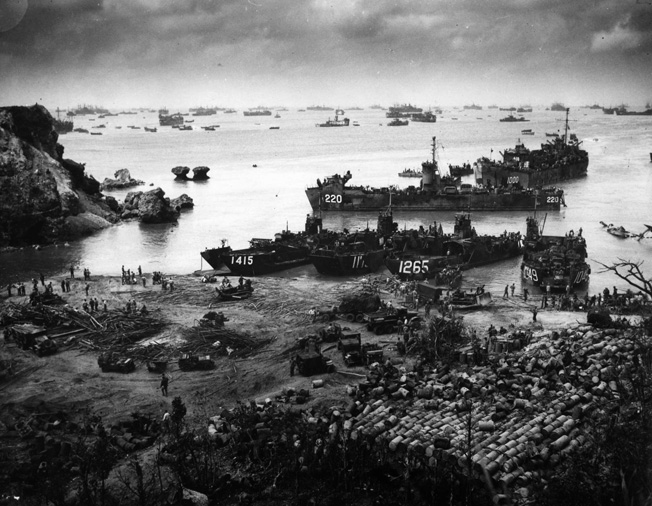 On April 13, 1945, almost two weeks after the initial U.S. landings on Okinawa, U.S. troops may be seen ashore while supply and transport vessels crowd the beach and stretch for miles out to sea.
