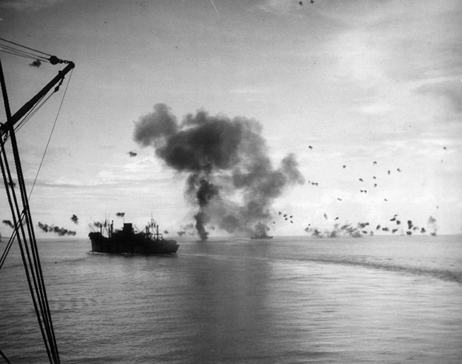The transport vessel USS President Jackson turns hard to port in the vicinity of the Solomons, while smoke rises from the cruiser USS San Francisco after a Japanese plane has crashed into its superstructure.
