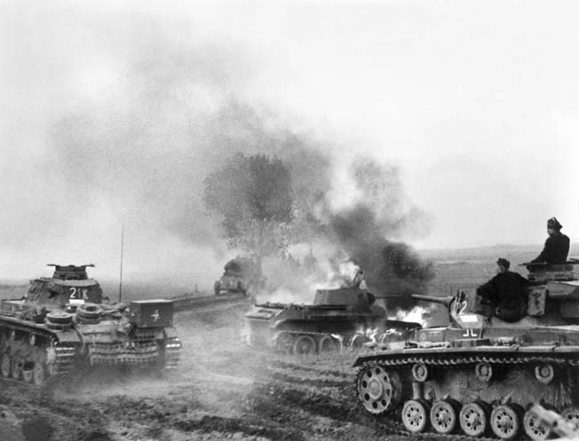 Tanks of German Army Group South's Panzer Group 1 pass a burning Soviet tank along a dirt road in the Ukraine during late summer 1941.