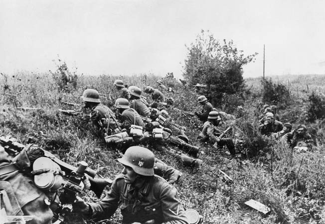 Crouching in the cover of a ditch, German infantrymen prepare to move out during an attack near the city of Kiev, capital of the Ukraine. A group of dazed Red Army prisoners sits farther down in the depression at right. Kiev fell to the Germans on September 19.