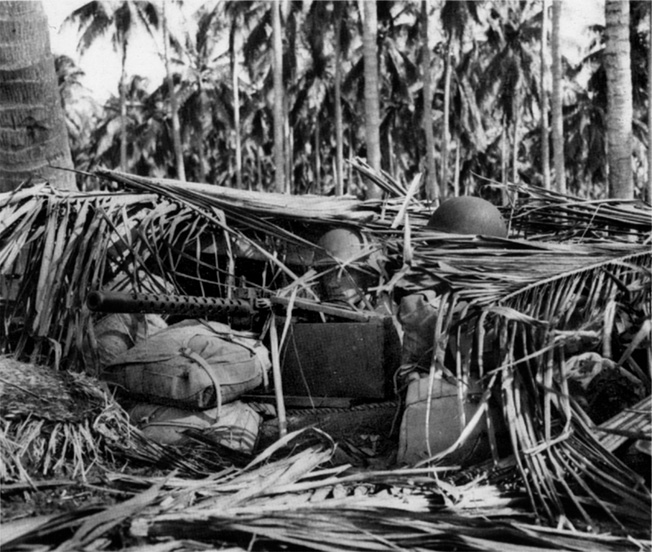 Camouflaged with palm fronds and reinforced with sandbags and coconut logs, a machine gun position on Guadalcanal is manned by alert Marines. During several massed attacks, waves of Japanese soldiers were mowed down by American machine guns.