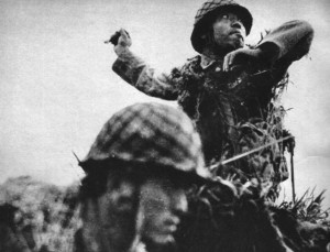 A Japanese soldier rises up to hurl a grenade while his comrade faces the enemy to his front. This photo was taken during the six months of bitter fighting on the island of Guadalcanal.