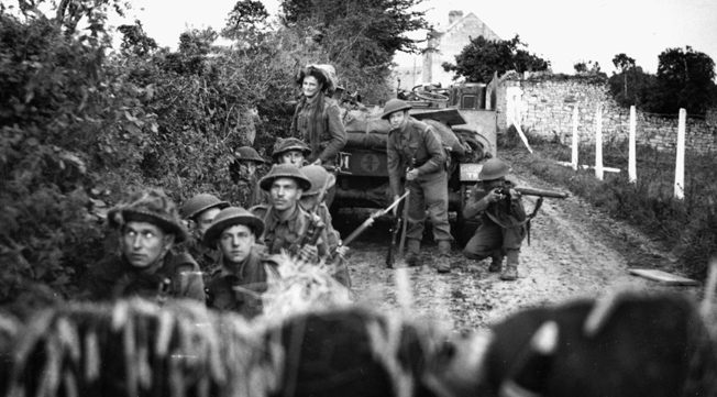With wary expressions, British infantrymen of the 130th Brigade, 43rd (Wessex) Division take cover in the shelter of a hedgerow during a mortar barrage, July 10, 1944. The 43rd Division was heavily engaged in the battle for Hill 112.