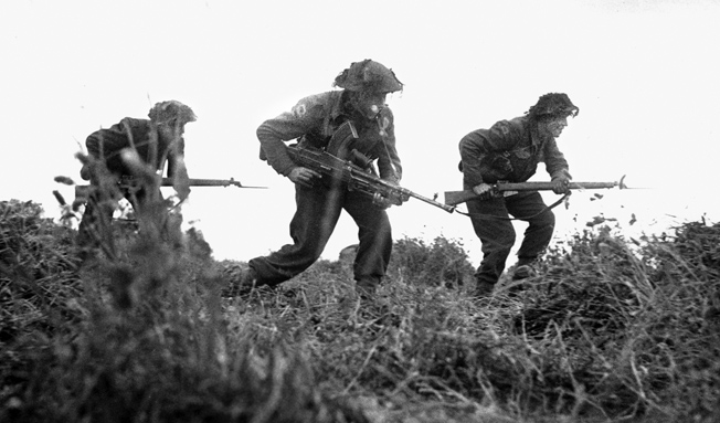 An infantry patrol from the British 8th Rifle Brigade, armed with Lee-Enfield rifles and a Bren gun, advances near Eterville, southwest of Caen, on June 29, 1944.