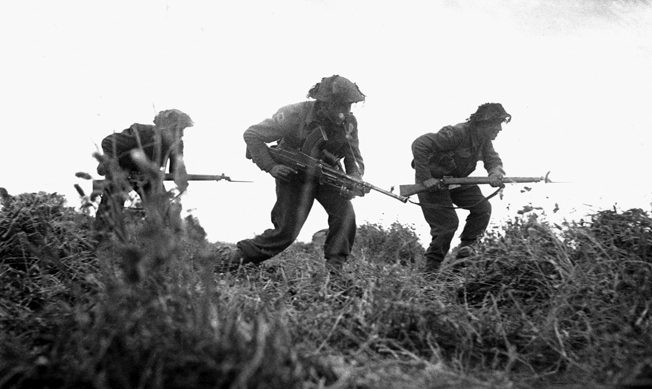 Three British infantrymen advance cautiously during a probe of German positions around the villages of Baron and Eterville southwest of Caen.
