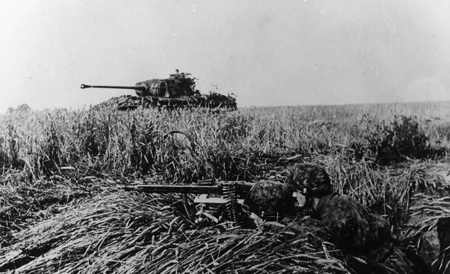 Supported by a Panther medium tank, a pair of SS panzergrenadiers man a well-camouflaged machine-gun position and await an Allied attack. This photo was taken in July 1944.