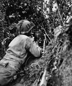 Well hidden by the foliage of a hedgerow in Normandy, an American machine gunner remains on alert during the attack near St. Lô, July 1944.