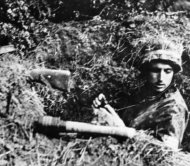 With his rifle and a Model 24 stick grenade, often called a potato masher, propped up on the edge of his foxhole, a German Fallschirmjäger waits for the American assault.