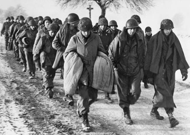 American soldiers captured during the early days of the Bulge are marched away from the front toward captivity in Germany. Thousands of Americans were taken prisoner during the fighting in Belgium and Luxembourg.