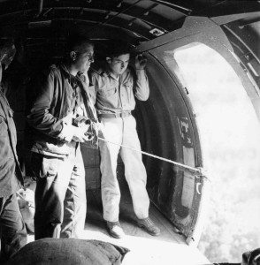 Standing in the open doorway of a C-47 transport on April 16, 1944, Brig. Gen. Frank Merrill, commander of the famed Marauders, watches the countryside of northern Burma pass below. At right is Sergeant Donald Ross, the dropmaster for the flight, which was en route to resupply Merrill's command.