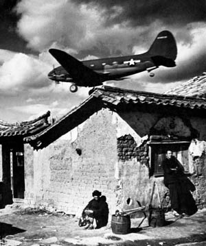 Coming in for a landing on an airfield near Kunming, China, a C-46 Commando transport plane flies low over the tile roofs of the nearby village.