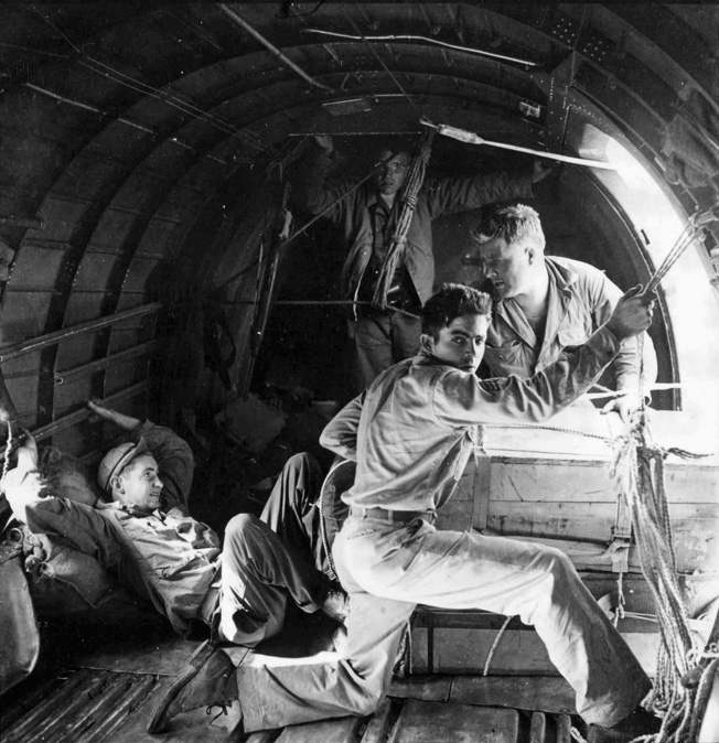 During the April 16, 1944 flight, Sergeant Donald Ross watches for a signal from the cockpit of a C-47. Private Robert Crane is positioned against the side of a box, ready to shove it out the door. Pfc. Charles Banks is positioned behind the bpx, while Brig. Gen. Frank Merrill observes.