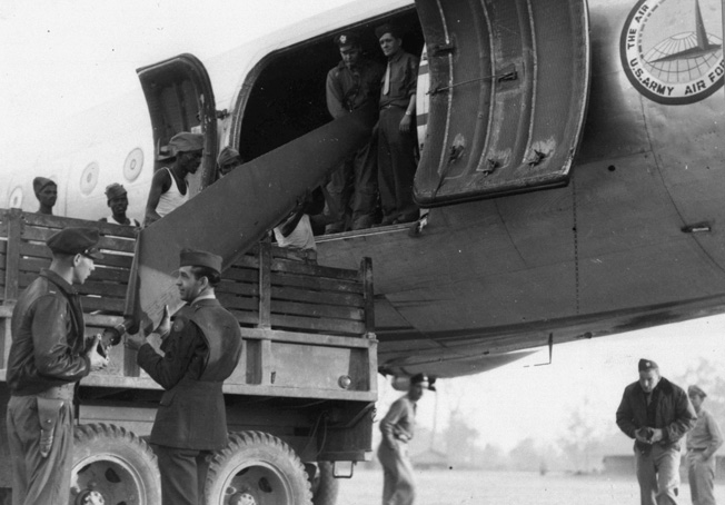 At Myitkyina, Burma, a helicopter is unloaded from a Douglas C-54 of the Air Transport Command. The helicopter saw limited use in the China-Burma-India Theater during World War II.