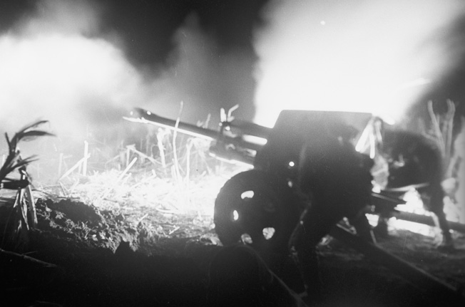 Bathed in the eerie, surreal light of muzzle flashes from nearby guns, a Soviet artillery crew services its weapon during a heavy barrage against suspected concentrations of German troops and armor in Hungary in March 1945.   ORIGINAL: Night barrage. Hungary, March 1945. The Great Patriotic War of 1941-1945.