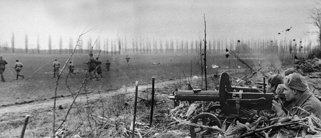 BELOW: A Red Army soldier mans his machine-gun position in Hungary while comrades, weapons at the ready, peer toward the horizon and the oncoming Germans. The machine gun, a Maxim Model 1910, appears anachronistic compared to modern German weapons.