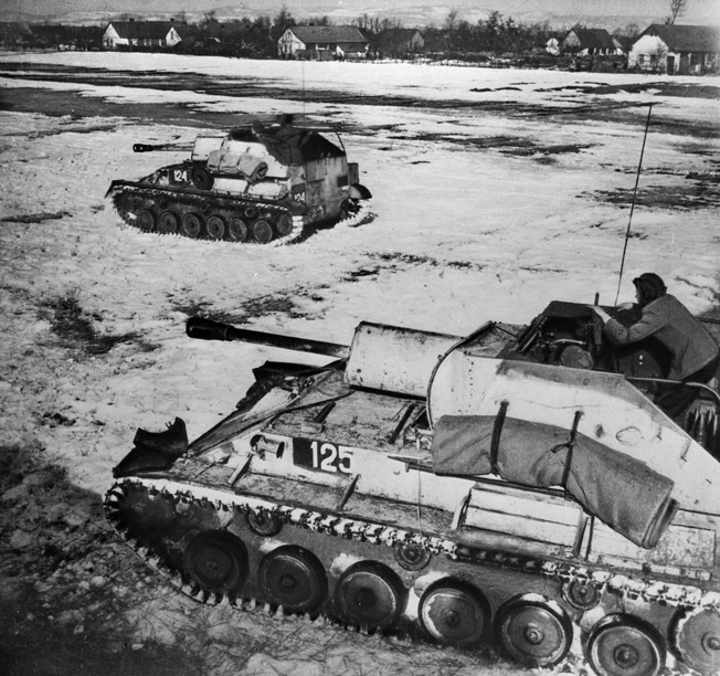 Soviet self-propelled guns advance warily across an open field in Hungary. As the Germans launched Operation Spring Awakening in March 1945, the Soviets had prepared an offensive of their own.