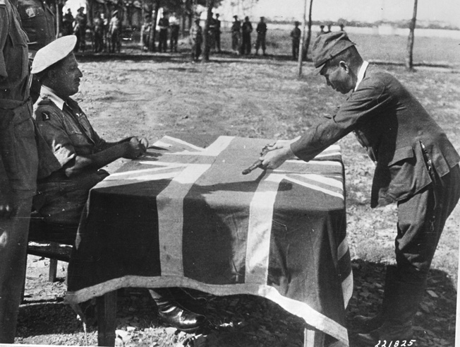 Major Ahmed Khan Sarda Bahadur of the 20th Indian Division sits before a table draped with the Union Jack and accepts the sword of a Japanese officer during surrender ceremonies in 1945.