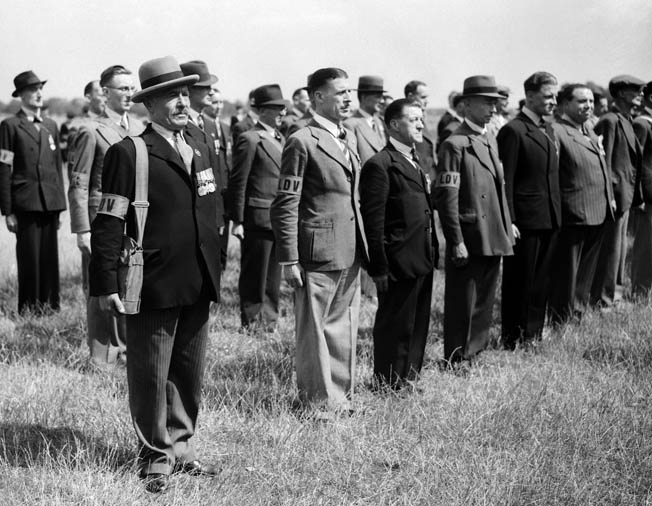 Originally called the Local Defense Volunteers, members of the Home Guard, some of whom served in the British armed forces during World War I, stand in ranks prior to inspection in July 1940.