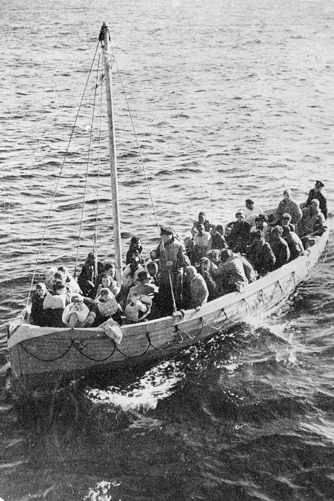 After being adrift eight days in the rough Atlantic, survivors of the sinking of the SS City of Benares are finally rescued. This boatload includes five children.