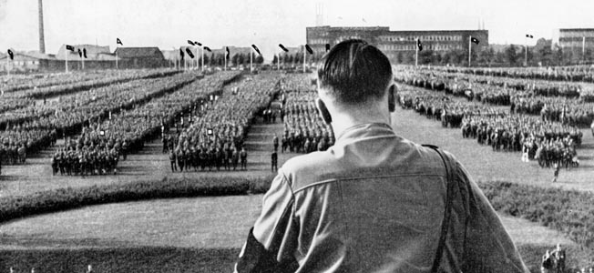 9-1933-7-9-A1-1 (100665) Hitler Addresses SA Groups / Photo /1933 National Socialism / SA meeting in Dort- mund on 9 July 1933. Hitler lists as tasks for the future: education acc.to NS ideas and elimination of unemploy- ment. - Hitler, on the platform, holding a speech for SA divisions. - Photo, 9 July 1933.