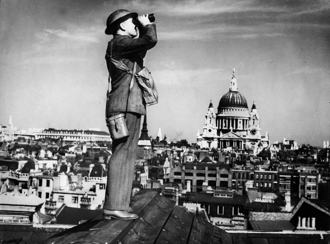The dome of St. Paul's Cathedral  looms in the background as a British  aircraft spotter scans the skies over London from a rooftop. False air raid alarms were common during the Phony War. Within months, however, London  would endure the Luftwaffe's Blitz.