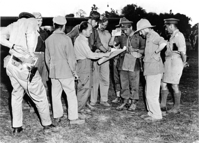 In this classic photograph, Brigadier General Orde Wingate is next to Brigadier Derek Tulloch at the far right. Majors Philip Cochran (back, facing camera) and John Alison are on the left. Major Alison is holding a map with Brigadier Scott, who wrote an account of this informal gathering. Air Marshal Baldwin and Brigadier Michael Calvert stand between Scott and Wingate.