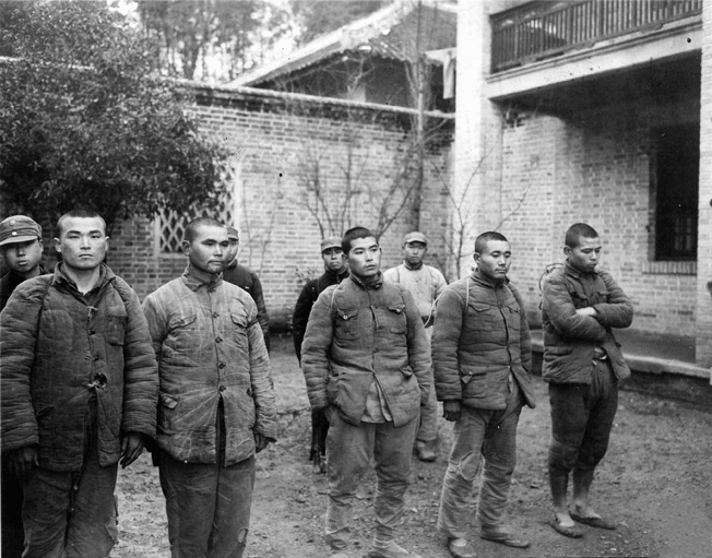 En route to the Chinese 74th Army headquarters at Wukong, five Japanese prisoners are marched out of the guerrilla headquarters at Tien Toh. All five appear to be well fed and clothed.