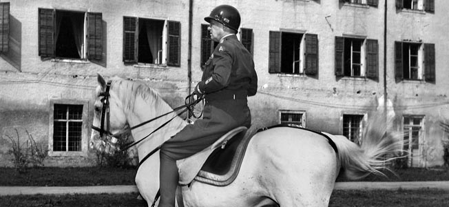 General George S. Patton, Jr. rides a stallion that Hitler intended to give to Japanese Emperor Hirohito. The patch on his shoulder representing Third Army would soon be replaced by a red and white octagonal patch representing the Fifteenth Army.