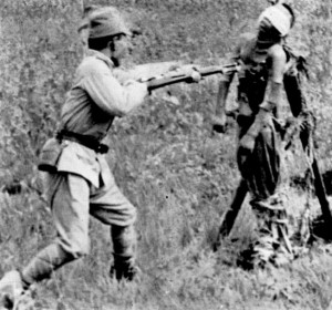 A Japanese soldier summarily bayonets a wounded Chinese prisoner. (National Archives)