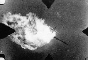 A Me-109 has its belly tanks set ablaze.