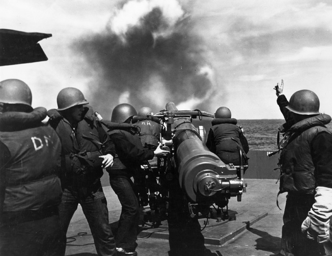 During gunnery practice at sea in September 1943, Naval Armed Guardsmen learn the finer points of operating the 4-inch deck gun aboard a merchant ship. Virtually unknown outside the Navy itself, Armed Guardsmen provided some measure of defense against enemy attack.