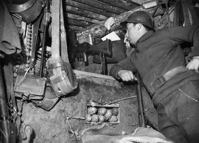 Maintaining watch toward German positions, a French soldier occupies an underground position on the Maginot Line during the Phony War. The line was built at great expense to France but was of little value against mobile German divisions when the shooting war began. Note the cache of hand grenades at center.