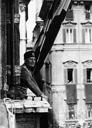 Dressed in full military uniform, a beaming Mussolini appears confident and resolute before a crowd of admirers.
