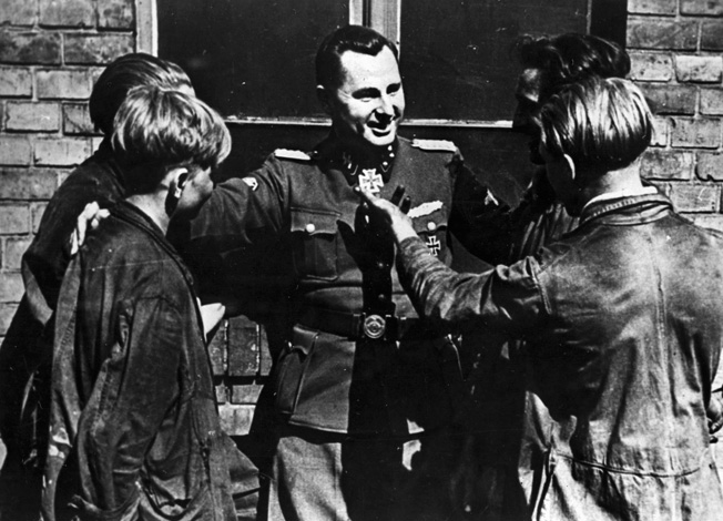 Belgian Nazi Leon Degrelle, a highly decorated combat veteran, talks with factory workers in his native country.
