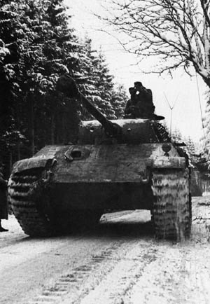 Its commander riding in the open air for better visibility, a German panzer rolls into Belgium in December 1944.