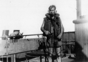 A combat-ready Naval Armed Guardsman is shown wearing his life vest and a gun station aboard his ship.