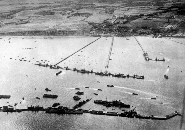 Shown deployed along a Normandy invasion beach, this Mullberry artificial harbor allowed supplies and reinforcements to be offloaded in support of the Allied landings which took place on June 6, 1944. This aerial view provides a perspective of the massive structure.