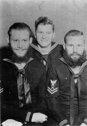 Three Naval Armed Guardsmen, their nonregulation hair and beards prominent, pose for a photo while on leave. Duty in the Armed Guard was acknowledged among the sailors as quite hazardous.