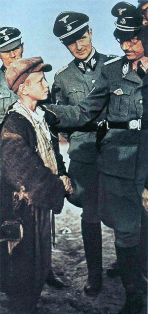Reichsführer SS Heinrich Himmler looks closely at a young Polish boy who has been judged as a potential candidate for a Nazi program to raise children from other countries as German, kidnapping them from their parents and placing them in the homes of loyal Nazis.