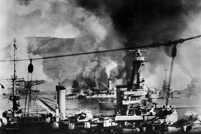 The elderly French battleship Provence is shown under fire in the foreground, while the modern battleship Strasbourg escapes toward the open sea at right, and another old battleship, Bretagne, burns furiously in the background during the Royal Navy attack on the French fleet at Mers el Kebir.
