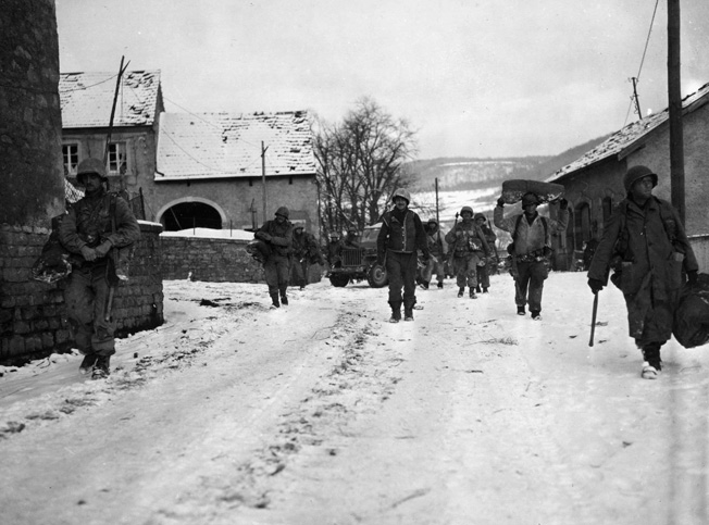 On January 21, 1945, soldiers of the U.S. 8th Infantry Regiment, 4th Infantry Division move cautiously through the town of Moesdorf, Luxembourg.