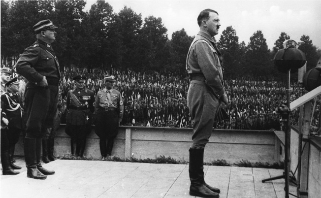 Hitler addresses an adoring throng during the Reich Party Rally of Victory held in Nuremberg from August 30 to September 3, 1933. Standing behind Hitler is his staunch supporter, Ernst Röhm, leader of the SA Stormtroopers who was murdered the following summer during the Night of the Long Knives.