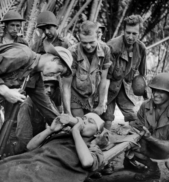 NEW GUINEA - 1943: Injured Korean, a captive slave laborer of the Japanese, getting care from American soldiers after being liberated by Allied forces. (Photo by George Strock/Time & Life Pictures/Getty Images)