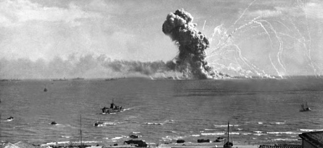 During the invasion of Sicily, an American cargo ship is hit by a bomb from a German plane and its cargo of munitions explodes, off Gela, Sicily, July 11, 1943.  Lt. Robert J. Longini.  (Army) NARA FILE #:  111-SC-180476 WAR & CONFLICT BOOK #:  1023