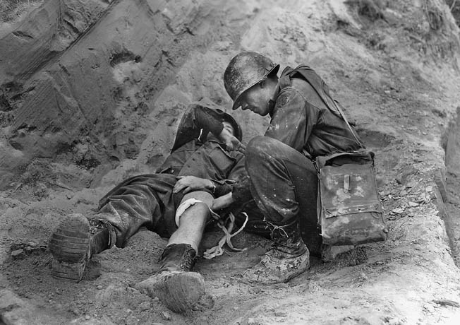 A wounded soldier from the 85th Division receives medical attention from an Army Corpsman.