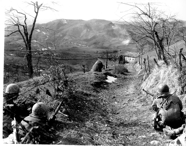 BELOW: In action on March 4, 1945, soldiers of the Company K, 87th Infantry Regiment, 10th Mountain Division, including two riflemen and a machine gunner, cover a roadway and the approaches to a farmhouse as other members of their squad rout Germans out of the building.
